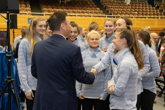 Bryan Felt is greeted by members of Seton Hall's women's volleyball team