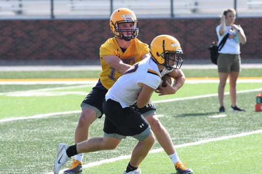 HSU's Brennen Wooten (12) hands the ball off to Cameron Woods during fall camp. Wooten is in the fourth stop of his collegiate career and set to start for the Cowboys on Saturday at Sul Ross State.