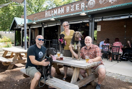 Owners of Hillman Beer Brad, left, Brandi, center, and Greig Hillman pose with their dogs Roland, Tulip and Hazel at the brewery on Aug. 16, 2019. The passing of Senate Bill 290 now allows pets inside breweries in North Carolina.