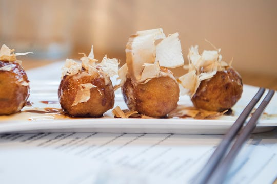 The Takoyaki Balls at Itto Ramen Bar and Tapas are made with chopped octopus, seaweed powder and brown rice flour then deep fried and topped with bonito flakes.