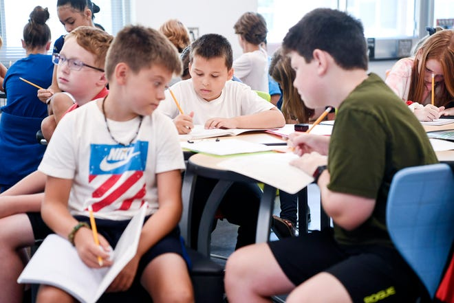 Buncombe County Schools fifth-graders write in composition books during the first day of school August 19, 2019.
