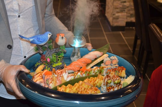 Johnny Liang serves his custom plate of sushi to a group of customers on Kume Hibachi & Steakhouse's opening day.