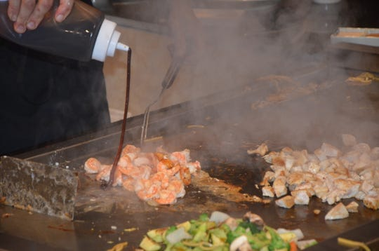 A chef at Kume Hibachi & Steakhouse marinates the shrimp before serving it to his customers.
