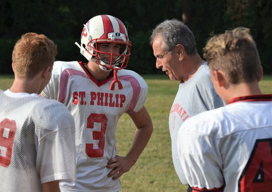 First-year St. Philip head coach Jeff Chadwick talks to the Tigers returning starting quarterback Conor Gausselin during preseason practices.