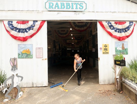Leah Cargile-Matteson, 10, sweeps shavings out of the rabbit barn as she and fellow 4-H members get the space ready for the Kitsap County Fair on Monday. Leah will be showing rabbits and cavies during the fair this week