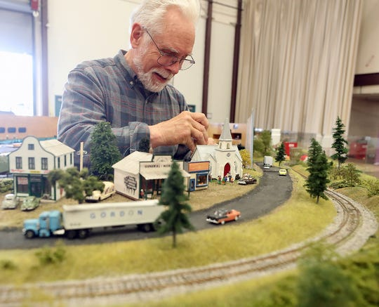 Tom Barrett, president of the Bremerton Northern Model Railroad, installs indicator lights behind the model train tracks on display at the Kitsap County Fair on Monday.