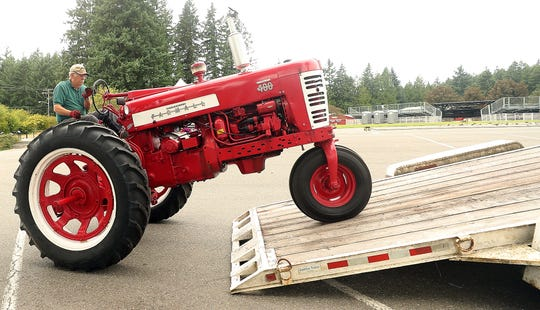 John Graham, of the Olympic Peninsula Antique Tractor & Engine Association, backs his 1955 Farmall tractor off of the trailer after his arrival at the Kitsap County Fair on Monday. The tractor will be on display during the fair.