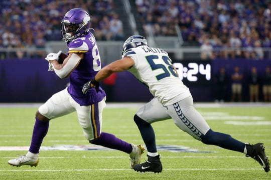 Minnesota Vikings tight end Irv Smith, left, runs from Seattle Seahawks outside linebacker Austin Calitro, right, after making a reception during the first half of an NFL preseason football game, Sunday, Aug. 18, 2019, in Minneapolis.