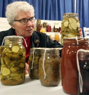 Midge Loser, of Bremerton, scrutinizes a jar of pickles while judging the preserved food entries in President's Hall at the Kitsap County Fair on Monday.