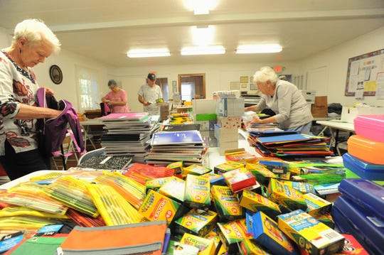 Volunteers from Hand in Hand in the Swannanoa Valley sort through school supplies on Aug. 16, when they met at Tabernacle United Methodist Church in Black Mountain before delivering the items to schools in the Owen District.