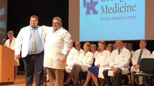 "Michael B. Kalfas embraces his father Dr. Mina ""Mike"" Kalfas during a white coat ceremony introducing the younger Kalfas and 34 other students to the first year of the new University of Kentucky College of Medicine's Northern Kentucky Campus."