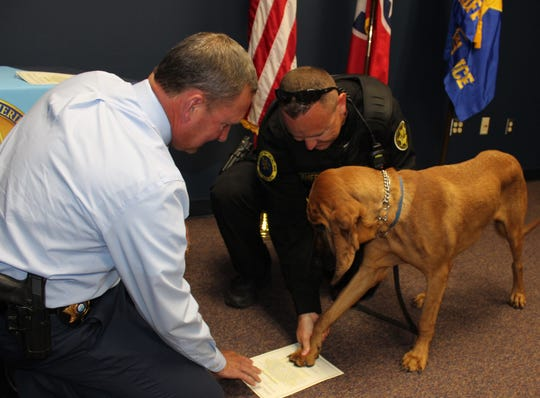 Sheriff John Fuson, left swears in K9 officer Roscoe, with paw assistance from handler Sgt. Eric Trout.