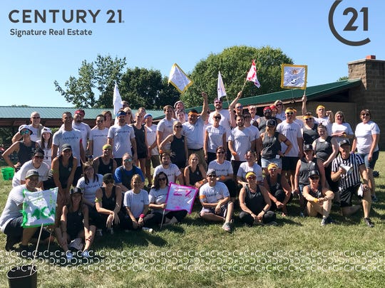 """Century 21 Signature Real Estate employees pose during their annual """"Office Olympics."""" It's one of the activities leadership says helps foster a community environment among employees."""