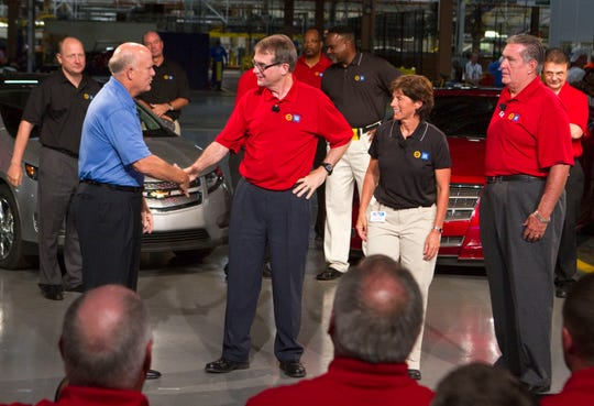 In this July 27, 2011, photo, General Motors Chairman and CEO Dan Akerson, from left, shakes hands with United Auto Workers President Bob King, marking the ceremonial start of labor negotiations between GM and the UAW as GM Vice President Labor Relations Cathy Clegg and UAW Vice President GM Joe Ashton look on. Ashton aide Jeff Pietrzyk is seen in the upper right corner.