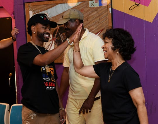 Big Sean high fives his mother, Myra Anderson, right, with his father, Jim Anderson, center, at a D.O.N. bowling party hosted by Big Sean at the Garden Bowl in Detroit on Aug. 18, 2019.