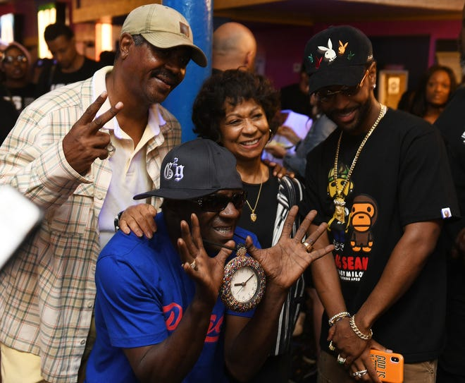 Flavor Flav, front, has a photo taken with Big Sean, right, and Sean's parents, Myra and Jim Anderson, at a D.O.N. bowling party hosted by Big Sean at the Garden Bowl in Detroit on Aug. 18, 2019.