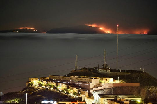 The fire on the mountains of the Canary Islands in this view taken from Santa Cruz de Tenerife island, Spain, early Monday, Aug. 19, 2019. Authorities on Spain's Canary Islands say around 4,000 people have been evacuated due to a wildfire that has ravaged more than 1,700 hectares (4,200 acres) since it broke out a day ago.