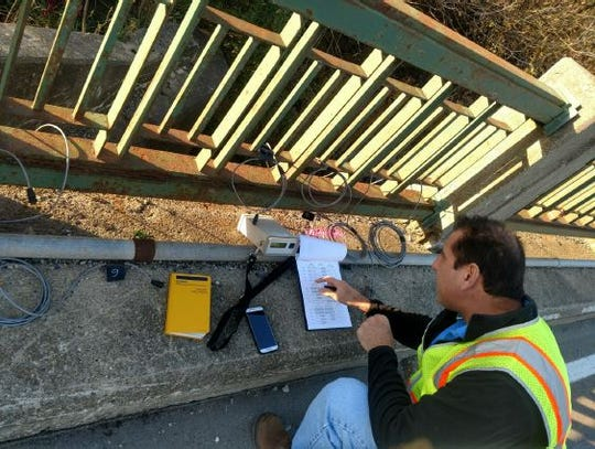 An inspector uses electronic sensors to test the peak stress capacity of a Midland County bridge.