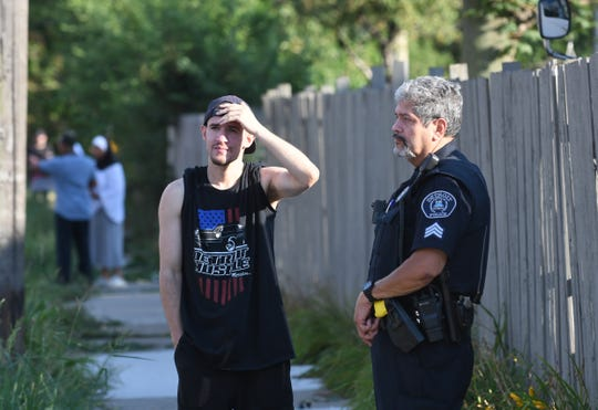 Edward Cruz of Detroit talks to a Detroit police officer moments after a 9-year-old girl was attacked by dogs.