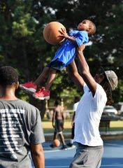 Roy Spear, 29, who lives in the neighborhood lifts up Bobby Weekly II, 4, towards the basket during a Basketball for All Neighbors Program at Delores Bennett Park in Detroit on Aug. 15, 2019. This is week five of a six week program sponsored by the Pistons, who are on track to restore 15 courts at 8 parks this summer as part of its community benefits commitment for the Pistons Performance facility
