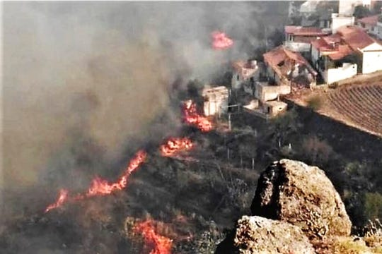 In this photo issued by Cabildo de Gran Canaria, flames from a forest fire burn close to houses in El Rincon, Tejeda on the Spanish Gran Canaria island on Sunday Aug. 18, 2019. Authorities on Spain's Canary Islands say around 5,000 people have been evacuated due to a wildfire that has ravaged more than 1,700 hectares (4,200 acres) since it broke out Saturday.