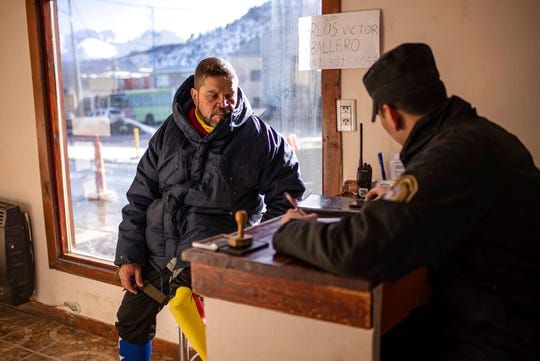 Venezuelan Yeslie Aranda registers his arrival at a police police station in Ushuaia, Argentina, the southernmost city in the world,  Saturday, Aug. 17, 2019.
