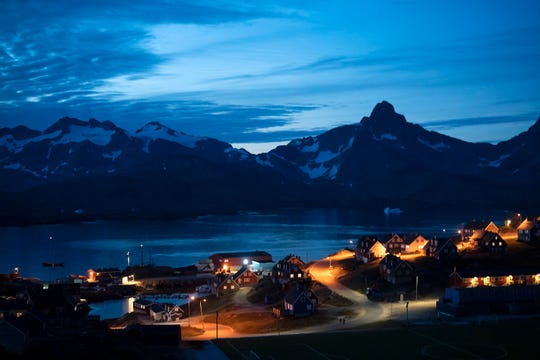 Homes are illuminated after the sunset in Tasiilaq, Greenland.