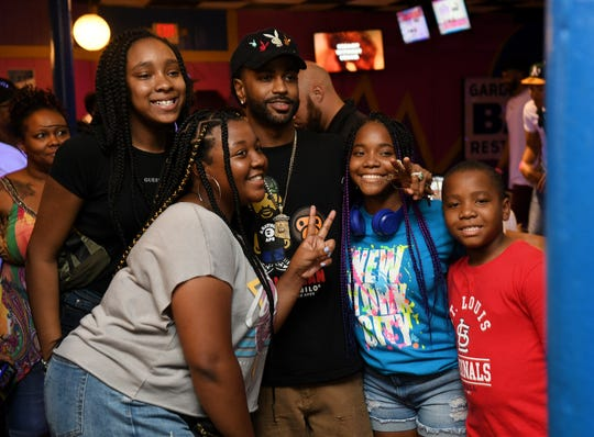 Takaya Sanders, 14, of West Bloomfield, left; and Chelsea Benton, 14, of Oak Park pose for a photo with Big Sean on Sunday with Makayla Franks, 15, and Cervantes Franks, 9, both of Oak Park at a D.O.N. bowling party hosted by Big Sean at Garden Bowl in Detroit.
