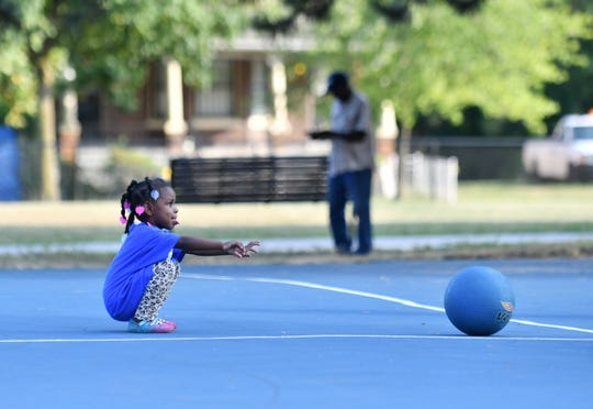 Dilyla Williams, 3, a resident of the nearby neighborhood, rolls a ball during a Basketball for All Neighbors Program at Delores Bennett Park in Detroit on Aug. 15, 2019. This is week five of a six week program sponsored by the Pistons, who are on track to restore 15 courts at 8 parks this summer, as part of its community benefits commitment for the Pistons Performance facility.