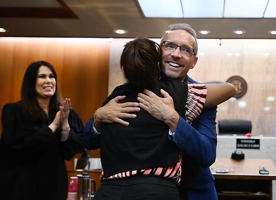 Former Ferndale Mayor Dave Coulter receives a hug from a well-wisher after being sworn in as Oakland County executive by Chief Judge Shalina Kumar, left, at Oakland County Circuit Court on Aug. 19, 2019.