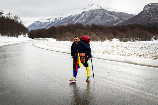 Venezuelan Yeslie Aranda, 57, walks on Route 3 between Tolhuin and Ushuaia, Argentina, Saturday, Aug. 17, 2019. Aranda left his hometown of San Cristobal in the southeastern state of Táchira last year with a backpack, $30 in his pocket and an aluminum prosthesis that enabled him to negotiate the continent's rugged roads.