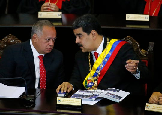 In this Jan. 24, 2019 file photo, Venezuelan President Nicolas Maduro, right, speaks with Constitutional Assembly President Diosdado Cabello at the Supreme Court during an annual ceremony that marks the start of the judicial year in Caracas, Venezuela.