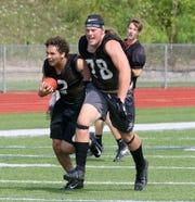 Ethan Simpson of the Elmira football team carries the ball behind Trey Hawken during practice Aug. 19, 2019 at Ernie Davis Academy in Elmira.