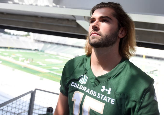 Light shines through onto Colorado State football player Collin Hill as he stands in the Canvas Stadium in Fort Collins for a portrait on Friday, Aug. 16, 2019.