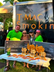Tom, left, and Becky McIntosh, right, show off some of the prizes their Sturgeon bay-based T-Mac Smokin team has won as four-time Grand Champions of Death's Door Bar-B-Q on Washington Island.