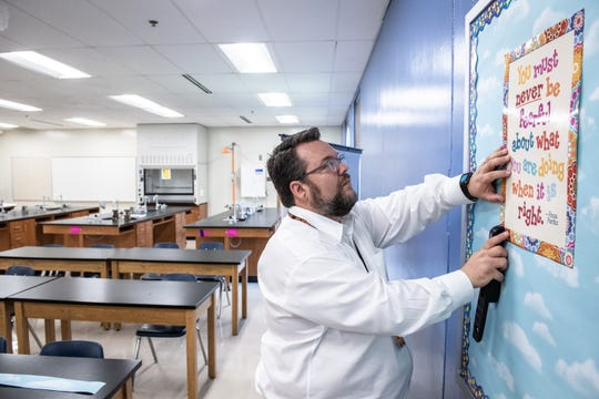 Scott Johnston, a first-year marine science and anatomy and physiology teacher at Southside High School in Greenville, decorates a bulletin board in his classroom Monday, August 19, 2019, for his first day of school with his student on Tuesday, August 20. Johnston left his career in business and retail to pursue a dream of becoming a teacher, earning his degree in biology from Bob Jones University and becoming certified through the Program of Alternative Certification for Educators (PACE).