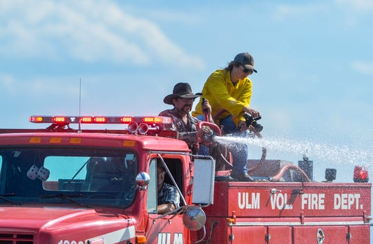 Volunteer firefighters from Ulm and firefighters from the Montana Air National Guard mop-up hot spots from a grass fire that burned in a pasture along I-15 in Ulm, Monday afternoon.