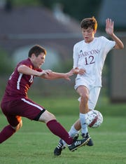 Henderson County's Rich Daniel (19) and Madisonville's Tate Young (12) battle for the ball at Colonel Field Thursday evening. The game ended in a 1-1 tie.