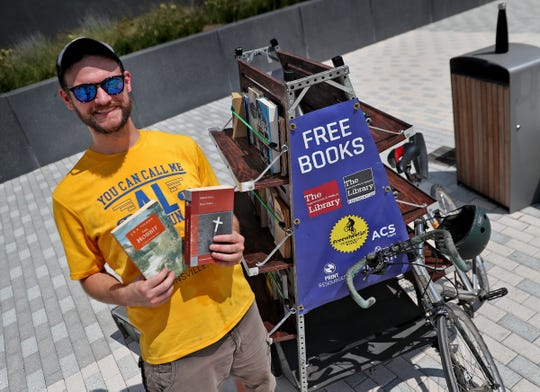 Josh Crain, Indianapolis Public Library's Decatur Branch manager, offers passers-by free books from the library's book bike on Aug. 19.