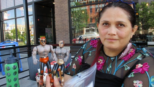 Artist Miriam Alarcón Avila holds up two  luchador action figures, Monday, Aug. 19, 2019.