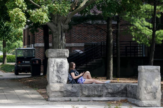 Charlotte Dickson, a first year nursing student, relaxes on a bench near Matthews hall on the first day of classes, Monday, Aug. 19, 2019 at Purdue University in West Lafayette.