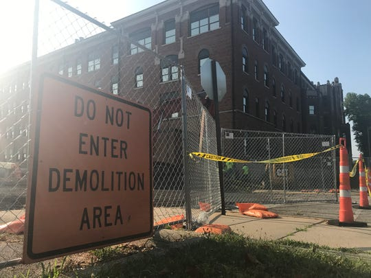 The grounds around the former St. Elizabeth Hospital have been fenced off for the demolition of the north and west wings of the facility, near the corner of North 14th and Hartford streets in Lafayette. Demolition is expected to continue through the end of the year.