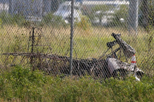 """The charred wreckage of a private plane is seen in a field near the Industrial Canal and New Orleans Lakefront airport, in New Orleans, Friday, Aug. 16, 2019. The city said on its """"Nola Ready"""" website that firefighters, emergency medical services and the police responded to the fatal crash Friday afternoon."""