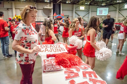 Ragin' Cajuns fans browse merchandise available to get autographed at the UL Fan Day on Aug. 18. UL could be in a financial bind after if ticket sales do not pick up for the Cajuns' season opener this weekend in the Mercedes-Benz Superdome in New Orleans.