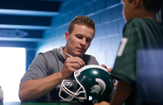 Brian Lewerke signs a helmet for a fan during the Meet the Spartans event, Monday at Spartan Stadium.