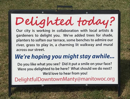 A sign in downtown Manitowoc about the city's collaboration with local artists and gardeners to beautify downtown.