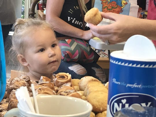"""Quinn Branham, 2 years old, ponders a muffin Monday morning at Marvin Memorial Library during the """"Boohoo-Yippee Breakfast."""""""