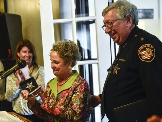 Pam Hall, left, former president of the Marion Area Chamber of Commerce, accepts a badge from Marion County Sheriff Tim Bailey during the chamber's 100th anniversary in March 2016. Bailey appointed Hall to be a special deputy for her work and support to consolidate the county's 911 emergency dispatch center. Hall died Sunday at the age of 67.