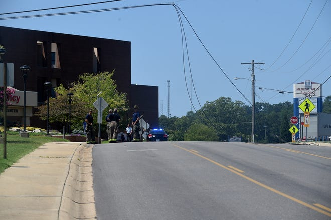 Firefighters and police wait outside Baxter Regional Medical Center for power company personnel to come fix power lines that were reportedly brought down by a dump truck. Traffic around Hospital Drive was still being rerouted as of 1:30 p.m. Monday.