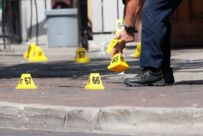 Authorities remove evidence markers at the scene of a mass shooting, Sunday, Aug. 4, 2019, in Dayton, Ohio.